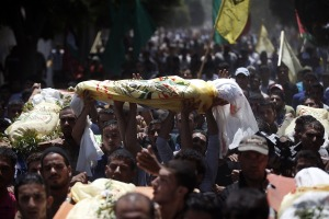 Relatives and friends of the al-Kaware family carry 7 bodies to the mosque during their funeral in Khan Yunis, in the Gaza Strip, on July 9, 2014. The father, a member of the Fatah movement, and his 6 sons were all killed the day before in an Israeli air strike that targeted their home. Credit: AFP/Thomas Coexthomas Coex/AFP/Getty Images/Used under a Creative Commons license